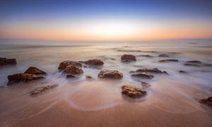 日出大海边时隐时现的乱石高清图片