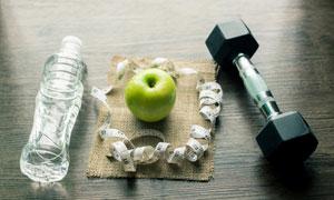 桌上哑铃苹果与一瓶水摄影高清图片