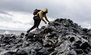 海边爬上礁石的背包客摄影高清图片