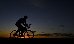 夕阳西下骑车人物剪影摄影高清图片