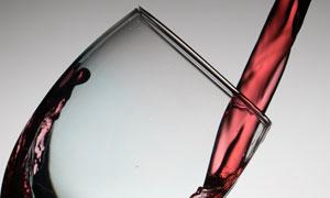 倒入高脚杯的红酒特写摄影高清图片