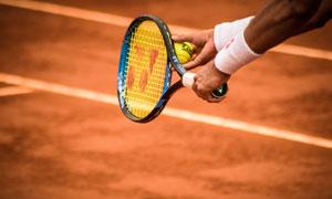 红土网球场上球员发球特写高清图片