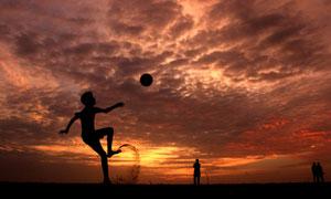 黄昏时在沙滩上踢球的儿童高清图片