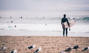 海边拿着冲浪板的男子摄影高清图片