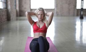 瑜伽垫上做卷腹的美女摄影高清图片