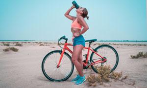 在骑车途中停下喝水的美女高清图片