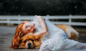 靠在狗狗身上的小女孩摄影高清图片