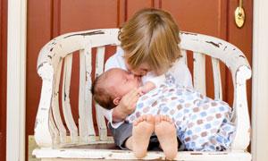 椅子上抱着宝宝的小孩摄影高清图片