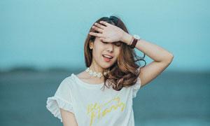 手遮擋陽光的卷發美女攝影高清圖片
