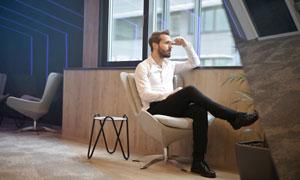 靠窗戶坐著的紳士男子攝影高清圖片
