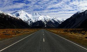 多云天空下的雪山道路摄影高清图片