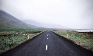 草地公路与浓雾之中的大山高清图片