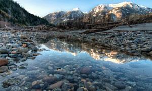 雪山与湖边浅滩处的鹅卵石高清图片