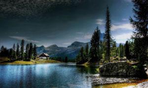 群山树木与湖边的小屋摄影高清图片