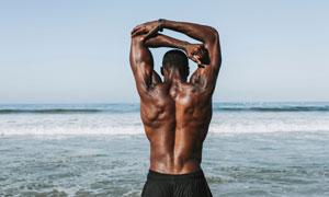 大海邊背部肌肉健碩的男子高清圖片