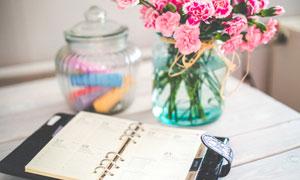 桌上的记事本与鲜花等摄影高清图片
