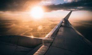乌云阳光下的飞机机翼摄影高清图片