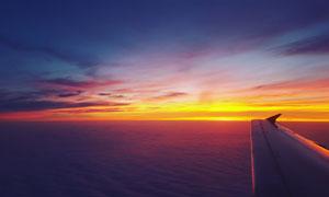 海面上低空飞行的飞机机翼摄影图片