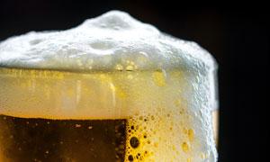 啤酒溢出的玻璃杯特写摄影高清图片