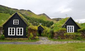 山脚下青草覆盖的房子摄影高清图片