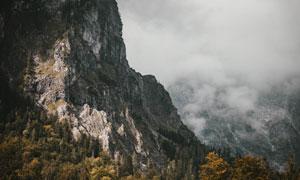 险峻高山与不断扩散的雾气高清图片