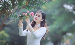 端詳著粉色鮮花的美女攝影高清圖片