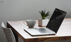 桌上的笔记本电脑与杯子等摄影图片