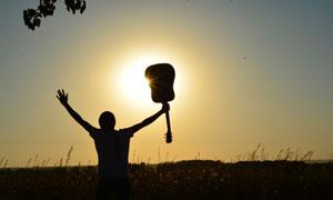高举小提琴的人物剪影摄影高清图片