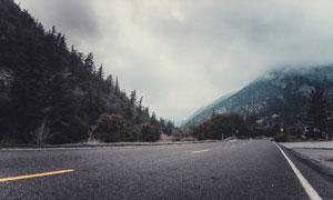 柏油路与雾气笼罩下的大山高清图片