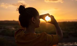 在对着太阳比心的女孩摄影高清图片