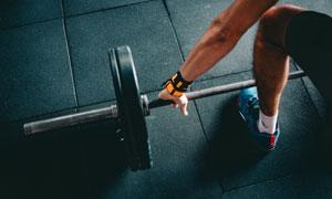 俯身抓杠铃的健身人物摄影高清图片