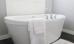 靠著墻擺放的潔白浴缸攝影高清圖片