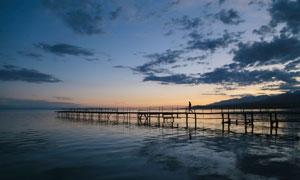 黃昏夕陽烏云與海上的棧橋高清圖片