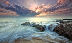 海水礁石與烏云后面的陽光高清圖片
