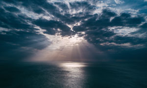 黑色云彩中透射下來的陽光高清圖片