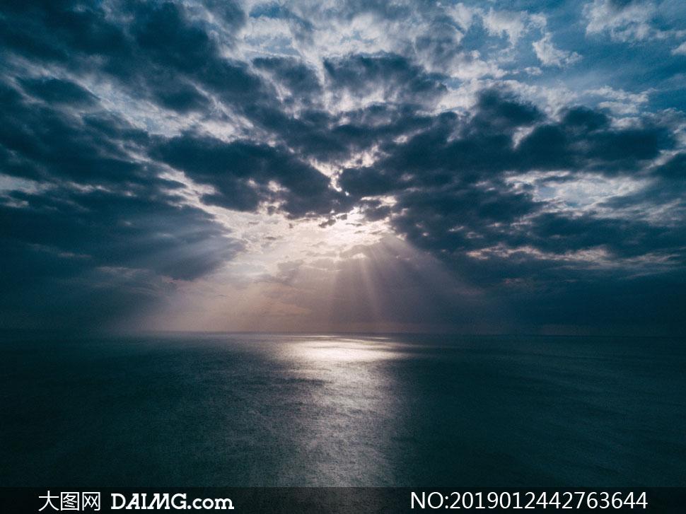 黑色云彩中透射下来的阳光高清图片