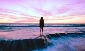 黄昏时海景晚霞与人物剪影高清图片