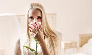 在闻着花香的金发女郎摄影高清图片
