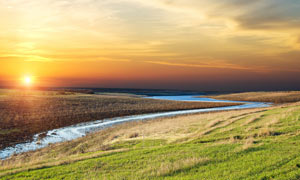 山坡下彎曲的小河夕陽美景攝影圖片