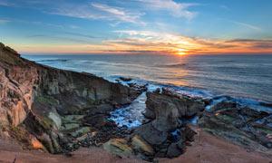 夕阳下的海边悬崖摄影图片