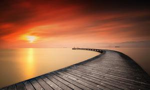 夕阳下海边木桥高清摄影图片