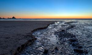 落幕下的海边沙滩景色摄影图片