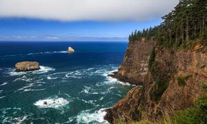 蓝天下的海边悬崖摄影图片