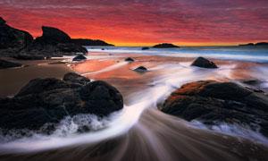 黄昏下海边海浪和礁石摄影图片