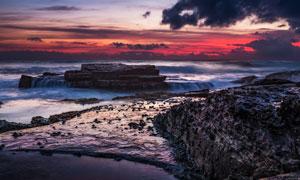 黄昏下海边海浪冲击着岩石摄影图片