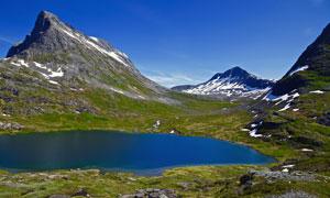 蓝天下雪山脚下蓝色湖泊摄影图片