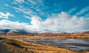 蓝天下的雪山草地摄影图片