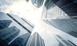 多云天空下的城市建筑仰视高清图片