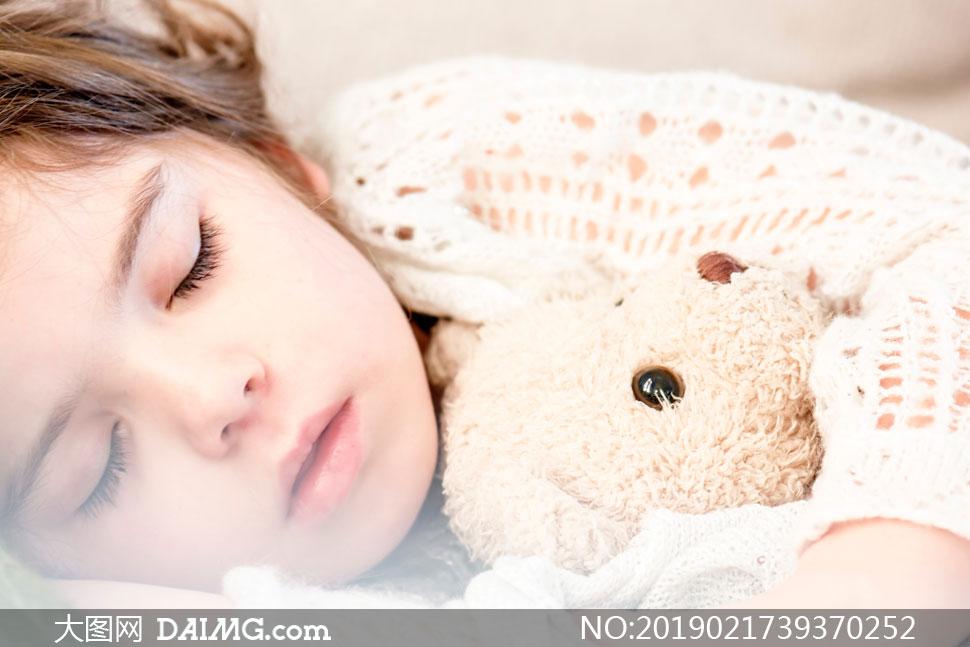 抱着玩具熊入眠的女孩摄影高清图片