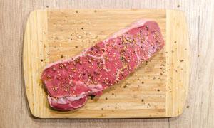 砧板上正在腌制的牛肉摄影高清图片
